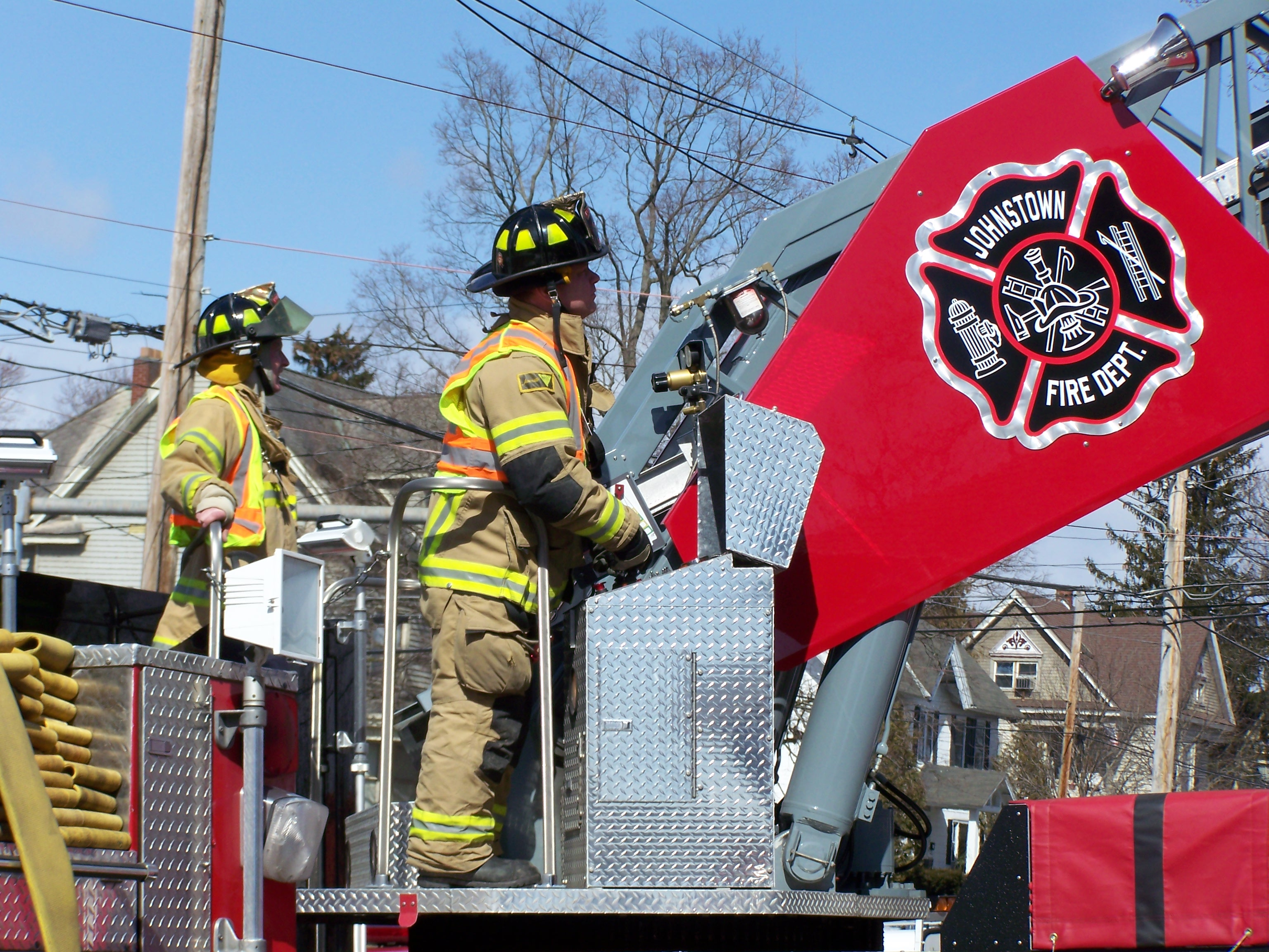 Firefighters on truck by flag